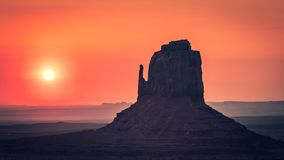 Sunrise behind the East Mitten, Monument Valley. A beautiful orange sunrise behind the East Mitten Butte in Monument Valley, Utah Arizona border royalty free stock photo