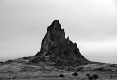 Monument Valley, Utah, a Jagged Butte Pierces the Sky in Stunning Monochrome. The knife-edged jags of a craggy butte stands sentry in a desolate landscape near Stock Photography