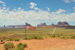 The Monument Valley. A view of the Monument Valley with the american flag Stock Photography