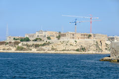 Monumental buildings and modern cranes on the beach Royalty Free Stock Photography