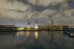 Monumental Cranes at sunrise in Shipyard. Night activity at the naval factories surrounding the city of Bilbao, Spain Royalty Free Stock Image