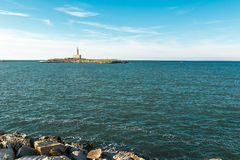 Monumental lighthouse on small island surrounded by blue sea Stock Photos