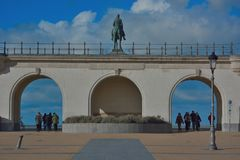Monumental statue of king Leopold the second, ancient king of Belgium on his horse. And unidentifiable people crossing the bridges , road to the sea at Ostend Stock Images