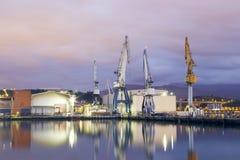 Monumentale Kräne bei Sonnenaufgang in der Werft Stockfotografie