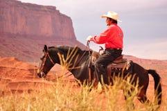 Monumentdal, Utah - September 12: Den stam- monumentdalen parkerar i Utah USA på September 12, 2011 Cowboy på häst i berömd tr Royaltyfria Bilder