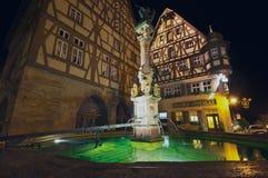 Monumenti storici con la fontana alla priorità alta alla notte in Rothenburg Ob'Der Tauber, Germania Immagini Stock