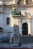 Monumento al caballero en armadura y un trabajador en el balcón foto de archivo
