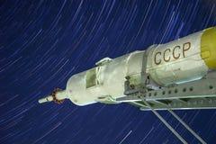 Monumento al razzo di Soyuz Terza fase Veicolo spaziale con equipaggio Fondo di Startrails immagini stock libere da diritti