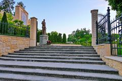 Monumento con un mazzo delle rose nella priorità alta all'entrata al parco Immagini Stock