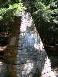 Monumento con una molla nella foresta Immagine Stock