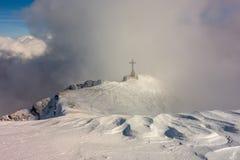 Monumento cruzado en un canto de la montaña rodeado por las nubes fotografía de archivo libre de regalías