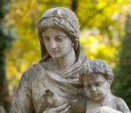 Monumento da mulher com a criança em um cemitério Imagens de Stock