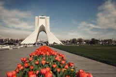 Monumento de Azadi de Tehran atrás das tulipas vermelhas editadas com o filtro do vintage de Brown Fotografia de Stock