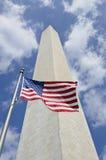 Monumento de Washington con el indicador americano en frente Imágenes de archivo libres de regalías