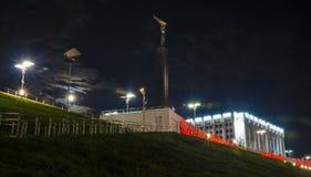 Monumento di gloria sotto forma di stele con un uomo con le ali in sue mani e di costruzione di governo alla notte in samara fotografie stock libere da diritti