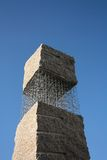 Monumento di pietra astratto sui nastri metallici Immagine Stock Libera da Diritti