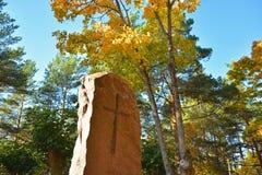 Monumento di pietra con un incrocio nel parco di autunno al monastero immagine stock