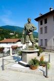 Monumento di un uomo con la valigia e un cappello su un piedistallo nel centro della città di Valli del Pasubio in Italia Fotografie Stock