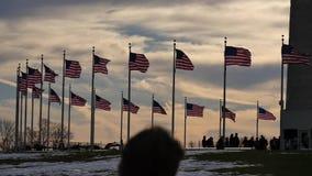 Monumento do céu azul do vento da bandeira do monumento de Washington grande contra o sol vídeos de arquivo