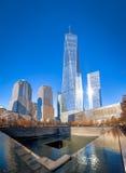 9/11 monumento en el punto cero del World Trade Center con una torre en el fondo - Nueva York, los E.E.U.U. del World Trade Cente Imagenes de archivo