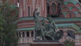 Monumento a Minin e a Pozharsky no fundo da catedral da manjericão do St em Moscou no quadrado vermelho video estoque