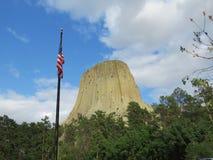 Monumento nacional de la torre de los diablos con los árboles de pino y la bandera americana Foto de archivo libre de regalías