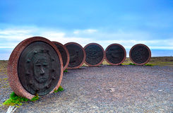 Monuments of circle figures. Norway. Monuments of circle figures with engraved funny faces, with are placed on asphalt plate. Outdoor. Backdrop of blue sky Royalty Free Stock Photography