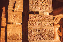 Monuments with columns and birds on reliefs of 7th century Hindu temple, town Badami, India Stock Photos