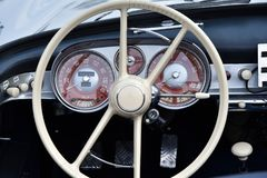 Vintage supercar interior. MONZA, ITALY - MAY 19 : classic car interior with close-up on steering wheel. Car in old racing car in rally `Mille Miglia` 2018 the Stock Images