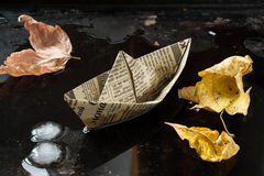 The mood of autumn: the boat from newspaper and leaves in a pudd Royalty Free Stock Photos