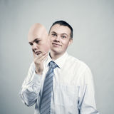 Mood changes. Businessman removes the mask from the face of a bad mood stock photos