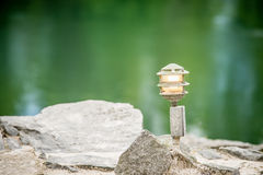Mood lighting light fixture on rocks the water Stock Photos