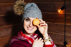 The mood of winter. Young beautiful dark-haired woman smiling in  clothes and cap with tangerines on wooden background. Young beautiful dark-haired woman Royalty Free Stock Photo