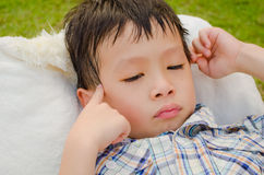 Moody asian boy. Moody young asian boy lie on a chair Royalty Free Stock Photo