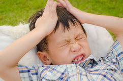 Moody asian boy. Moody young asian boy lie on a chair royalty free stock photos