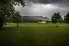 Moody cabin in an empty field Stock Image