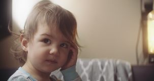 Moody and cinematic shot of baby girl at home on couch. Shot in 4K RAW on a cinema camera stock video