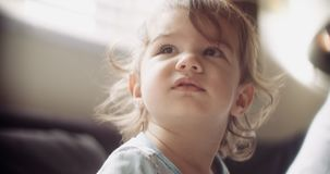 Moody and cinematic shot of baby girl at home on couch. Shot in 4K RAW on a cinema camera stock footage