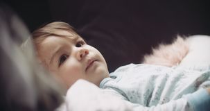 Moody and cinematic shot of baby girl at home on couch. Shot in 4K RAW on a cinema camera stock video footage