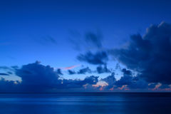 Moody clouds over the sea at dusk. Beautiful light and colours of moody clouds over the midnight blue sea in Maldives. Long Exposure stock image