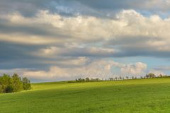 Moody cloudy sky over green hills. And country road royalty free stock images