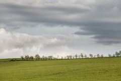 Moody cloudy sky over green hills. Orton effect image royalty free stock image