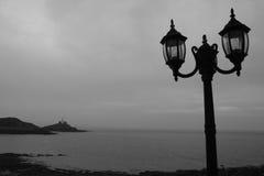 Moody coastal lampposts. Moody shot of lapmpost and the coastline at the mumbles, wales royalty free stock photos