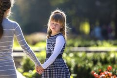 Moody cute child girl holding mother hand looking back on warm day outdoors. Family relationship and recreation.  stock photo