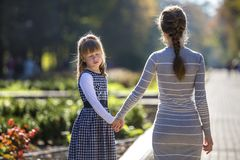 Moody cute child girl holding mother hand looking back on warm day outdoors. Family relationship and recreation.  royalty free stock image
