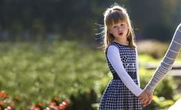 Moody cute child girl holding mother hand looking back on warm day outdoors. Family relationship and recreation.  stock photography
