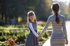 Moody cute child girl holding mother hand looking back on warm day outdoors. Family relationship and recreation.  royalty free stock photos