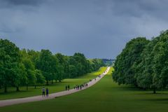 A Moody Day at The Long Walk in Windsor Great Park. A small patch of sun light spills over the Long Walk in Windsor Great Park, England. The approaching storm is stock photography