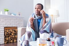 Moody depressed man having fever. High body temperature. Moody depressed ill man holding his smartphone and making a call while having a fever Royalty Free Stock Images