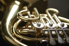 Moody detail of french horn. Close up of instrument with dark background Royalty Free Stock Photos